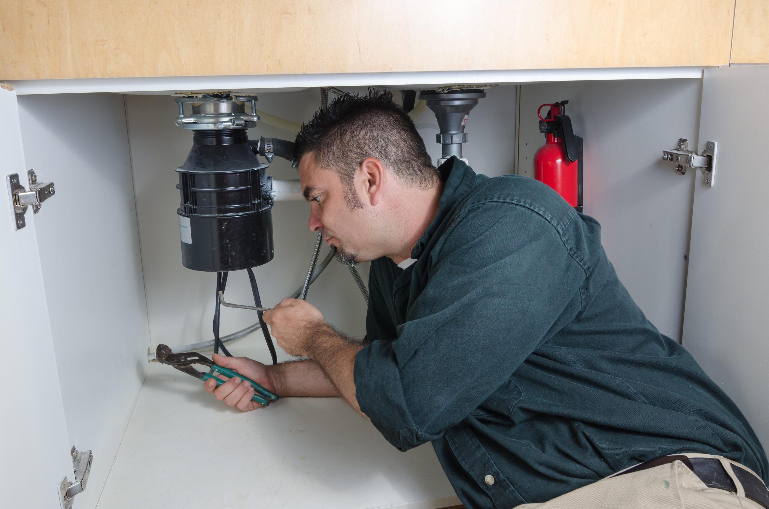 technician servicing sink garbage disposal