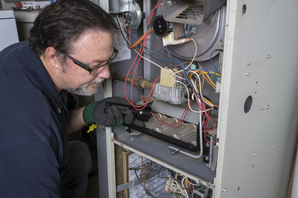 technician servicing a furnace