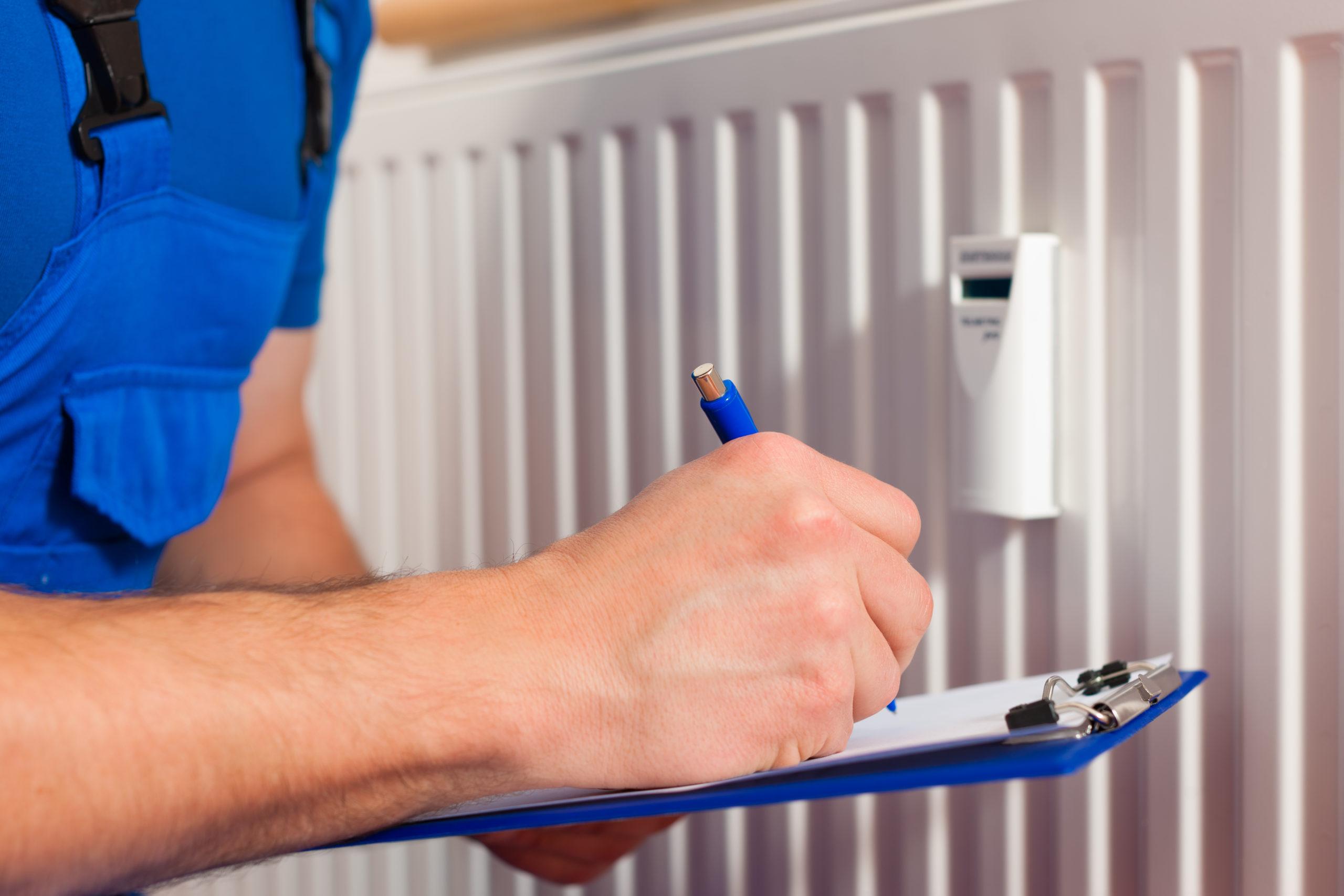 technician reading the heat meter on a heater